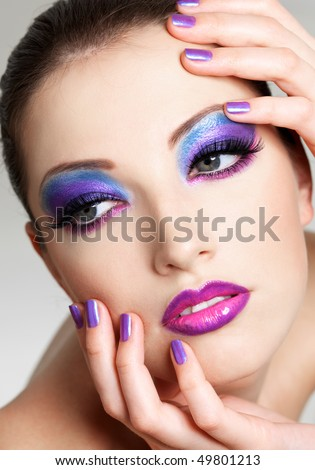 Beautiful  female face with fashion  make-up of eyes and beauty purple manicure. She put her hands on face.