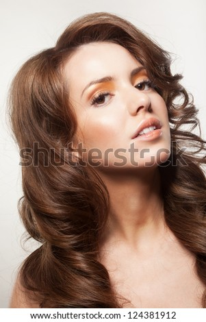 beautiful female face with make-up and shiny curly hair. Elegant hairstyle for long hair