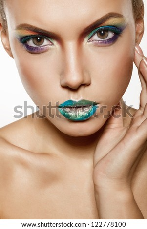 beautiful female face with rainbow makeup. girl touch her face by hand