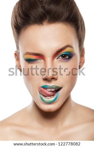 beautiful female face with rainbow makeup. girl winking and showing tongue