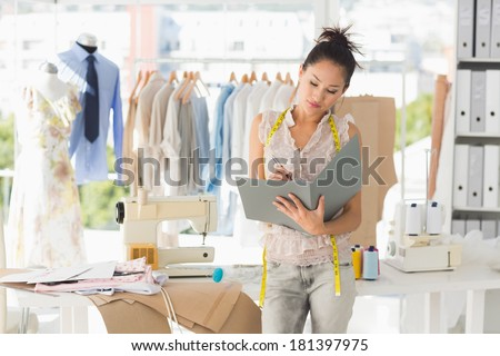 Beautiful female fashion designer looking at folder in the studio