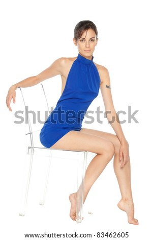 Beautiful female fashion model posing sitting on transparent chair, over white background