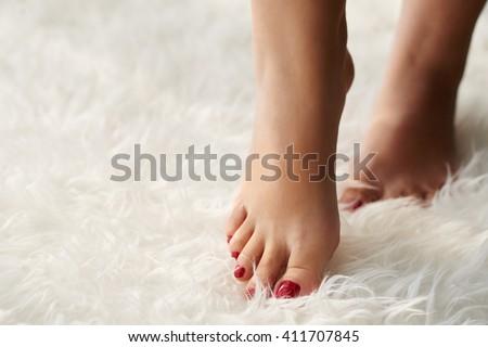 Beautiful female feet of white fake fur carpet