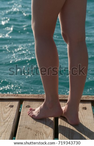 Beautiful female feet stand on a wooden pier. #719343730