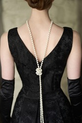Beautiful female figure from the back in a black dress and pearls in the style of 20-30 years of the XX century