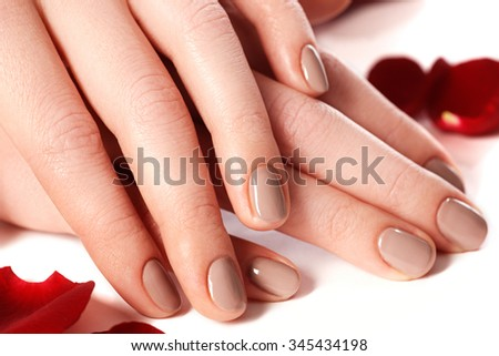 Beautiful female finger nails with natural nail closeup on petals. Perfect manicure. Woman hands with manicure natural nails closeup and rose. Skin and nail care.