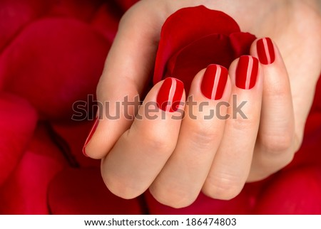 Beautiful female finger nails with red nail closeup on petals. Perfect manicure