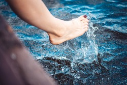 beautiful female foot plays with water and makes splashes in the lake