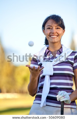 Beautiful female golf player playing with the ball