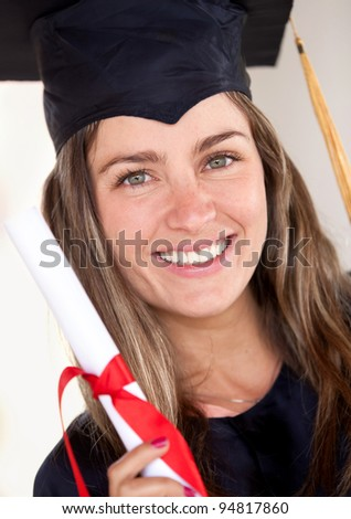 Beautiful female graduate holding her diploma and smiling