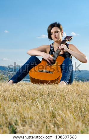 Beautiful female guitarist playing acoustic guitar on field against blue sky