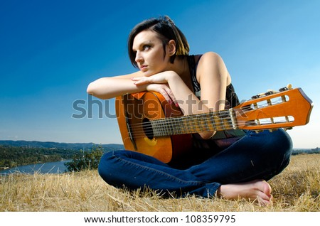 Beautiful female guitarist sitting and posing with acoustic guitar on field against blue sky. Wide angle.
