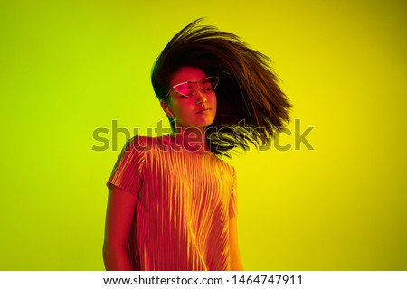 Beautiful female half-length portrait isolated on yellow studio background in neon light. Young emotional woman. Human emotions, facial expression concept. Dance in eyeglasses and wireless headphones.