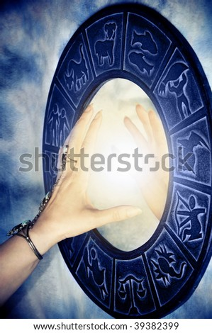beautiful female hand touching magic mirror with zodiac symbols and light