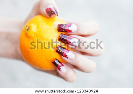 Beautiful female hand with unique curtain nail art design holding an orange