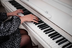 Beautiful female hands over the piano keys. A white musical instrument.