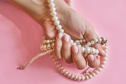 Beautiful female hands with manicure holding pearls. Woman showing hands with stylish trendy female manicure. Hand skin care