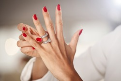 Beautiful female hands with red nails and elegant diamond rings.