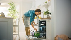 Beautiful Female is Loading Dirty Plates into a Dishwasher Machine in a Bright Sunny Kitchen. Girl in Wearing an Apron. Young Housewife Uses Modern Appliance to Keep the Home Clean.