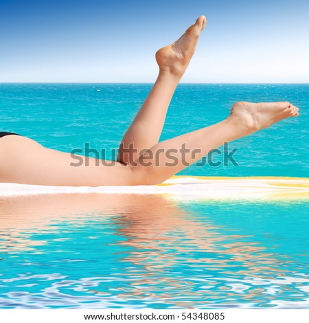 beautiful female legs between a pool and sea