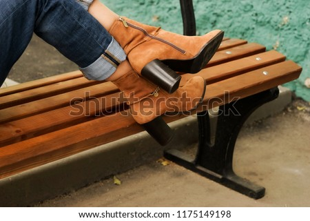 beautiful female legs in autumn high heels boots in the street. fashion background. woman sits on a wooden bench. copy space