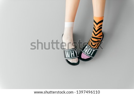 Beautiful female legs in missmatched teen socks wearing fashionable rubber slippers with inscription why not on gray background. Elegant stylish trendy and voguish footwear for fashionable ladies
