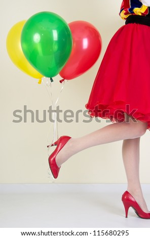 Beautiful female legs in red shoes and balloons, got hold of the heel shoes.