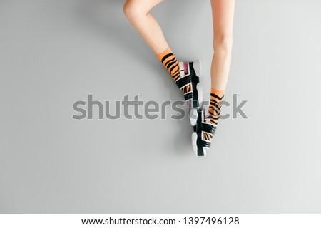 Beautiful female legs in striped orange trendy socks wearing fashionable black white high wedge leather sandals. Stylish womens footwear. Elegant girls legs in odd high sole shoes on gray background