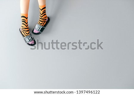 Beautiful female legs in striped trendy orange socks wearing fashionable rubber slippers with inscription why not on gray background. Elegant stylish trendy and voguish footwear for fashionable ladies