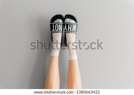 Beautiful female legs in white mesh teen socks wearing fashionable rubber slippers with inscroption why noton gray background. Elegant stylish trendy leg-wear . Voguish legwear for fashionable ladies