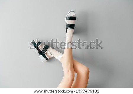 Beautiful female legs in white mesh trendy socks wearing fashionable black white high wedge leather sandals. Womens modern fashion footwear. Rebel girl in high sole stylish shoes on gray background