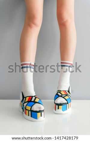 Beautiful female legs in white socks wearing super fashionable colorful high wedge sandals.  Trendy stylish womens footwear. Elegant girls legs in eccentric high sole sexy shoes on gray background