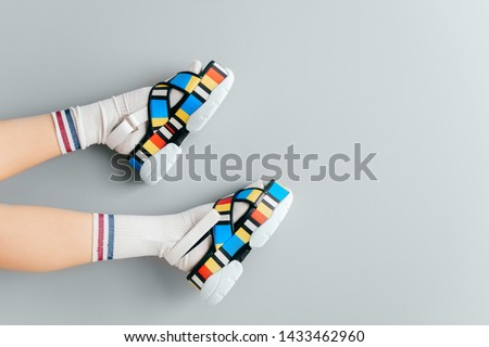Beautiful female legs in white trendy socks posing in colorful fashionable high wedge leather sandals on gray background. Asian anime style concept. Womens legs wearing high sole summer stylish shoes