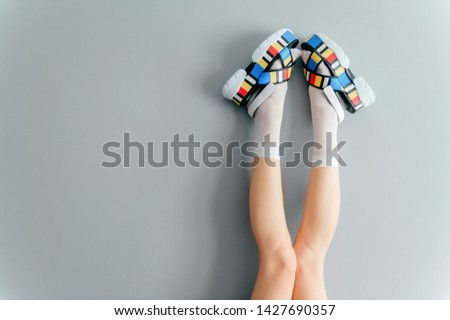 Beautiful female legs in white trendy socks posing in fashionable colorful high wedge leather sandals on gray background. Womens modern voguish footwear. Girl wearing high sole summer massive shoes.