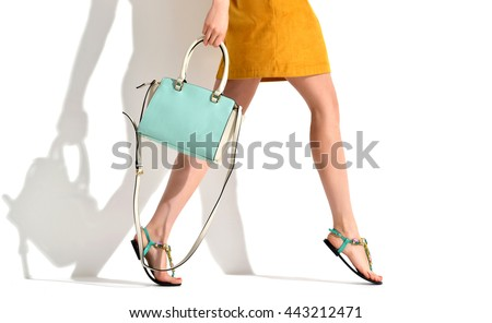 Beautiful female legs wearing summer shoes in brown yellow designers dress and blue mint woman clutch bag on white background