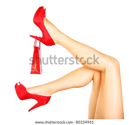 Beautiful female legs with red heels and shopping bag isolated on white background, money spending concept