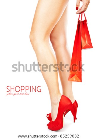 Beautiful female legs with red high heels holding shopping bags isolated on white background, money spending concept
