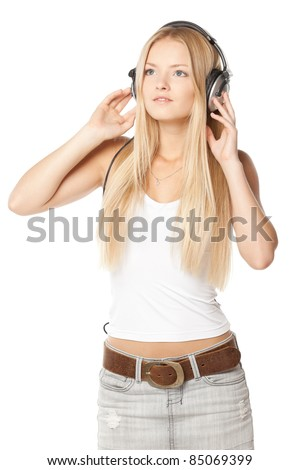 Beautiful female listening to the music on headphones over white background - stock photo