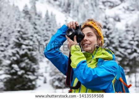 Beautiful female makes photo on professional camera, wears casual anorak and headband, enjoys beautiful mountains covered with snow, being active hiker. Making nice pics of wonderful landscape