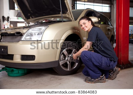 Beautiful female mechanic changing tire on car - stock photo