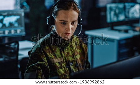 Beautiful Female Military Surveillance Officer in Headset Working in Central Office Hub for Cyber Operations, Control and Monitoring for Managing National Security, Technology and Army Communications.
