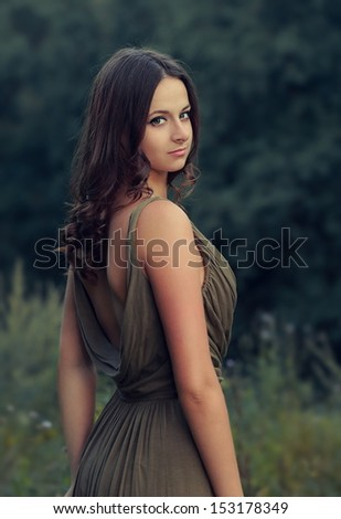 Beautiful female model in fashion dress outdoors summer background