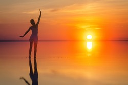 Beautiful female model open arms under the sunrise at seaside. Calm water of salt lake Elton reflects silhouette of woman. Sun goes under horizon. Girl stands alone in water