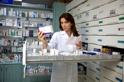 Beautiful female model pharmacist looking at medicine