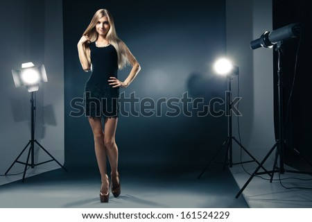 Beautiful female model posing at studio in the light flashes