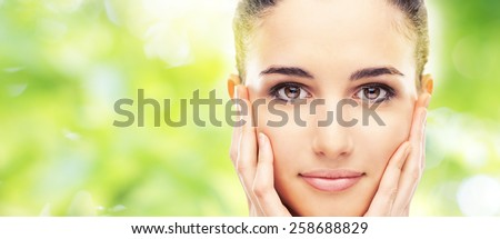 Beautiful female model touching her smooth glowing face skin and smiling at camera