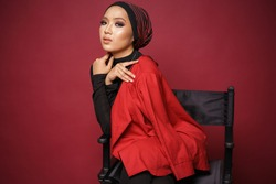 Beautiful female model wearing black shirt and red blazer with turban style hijab, sitting on a director chair isolated over red background. Muslim female fashion lifestyle portraiture concept.