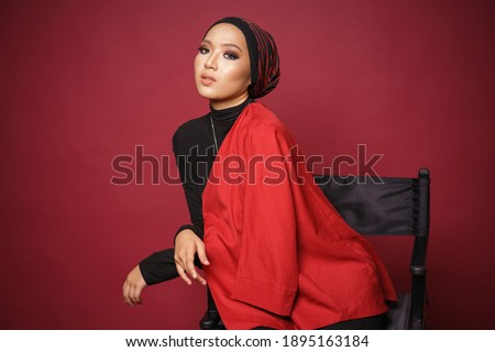Beautiful female model wearing black shirt and red blazer with turban style hijab, sitting on a director chair isolated over red background. Muslim female fashion lifestyle portraiture concept. Stockfoto ©