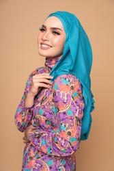 Beautiful female model wearing modern batik kebaya with hijab, an Asian traditional dress for Muslim woman isolated over beige background. Stylish Muslim female fashion lifestyle  concept.