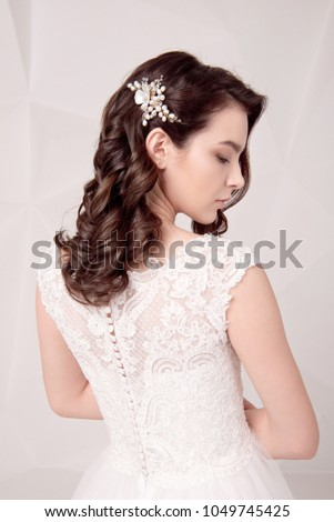Beautiful female model with perfect fashion makeup and hairstyle. Elegant female hairstyle.